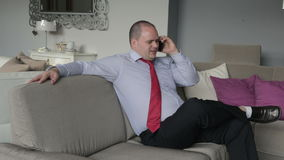Businessman talking on the phone in his living room and looks upset stock video footage