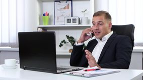 Businessman talking on phone in his office and smiling