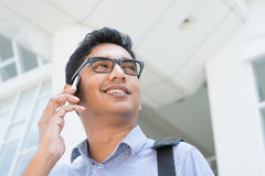 Businessman talking on phone. Indian businessman talking on phone in front modern office building Stock Image