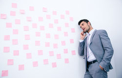 Businessman talking on the phone and looking on stickers Royalty Free Stock Image