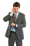 Businessman talking on phone and looking on watch Stock Photos