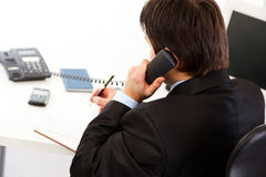 Businessman  talking on phone and making notes Royalty Free Stock Photo