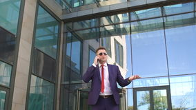 Businessman talking on phone near modern building. stock video
