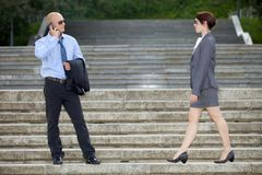 Businessman talking on phone next to businesswoman Royalty Free Stock Image