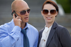 Businessman talking on phone next to businesswoman Stock Photography