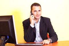 Businessman talking by phone opposite computer. Young businessman in a black suit working on computer and talking by mobile phone at office royalty free stock images