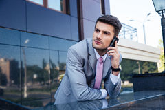 Businessman talking on the phone outdoors. Thoughtful businessman talking on the phone outdoors Royalty Free Stock Photo