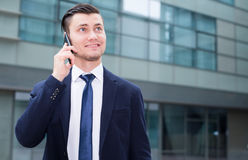 Businessman is talking phone. Outside the office Stock Images
