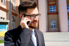 Businessman is talking on phone. Outside the office Royalty Free Stock Image