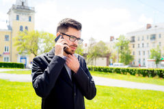 Businessman is talking on phone. Outside the office Stock Images