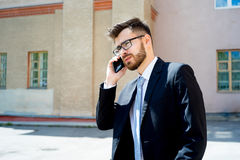 Businessman is talking on phone. Outside the office Royalty Free Stock Photography