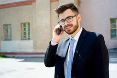 Businessman is talking on phone. Outside the office Royalty Free Stock Photo
