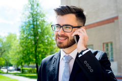 Businessman is talking on phone. Outside the office Stock Photo