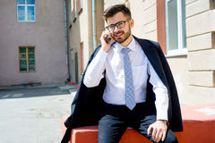 Businessman is talking on phone. Outside the office Royalty Free Stock Images