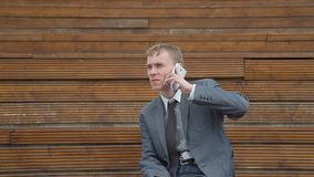 Businessman talking on the phone outside office. Businessman holding cup of coffe in his hand and talking on the phone outside office. Slow motion. Lifestyle and stock video footage