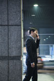 Businessman talking on the phone in a parking garage Royalty Free Stock Photography