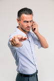 Businessman talking on the phone and pointing at camera Royalty Free Stock Image