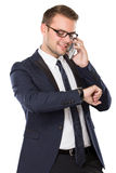 Businessman talking on the phone. Portrait of Businessman looking at his watch while speaking on the phone. isolated over white background Royalty Free Stock Photo