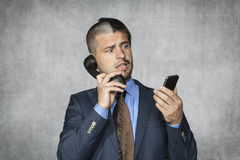 Businessman talking on the phone and reading email Royalty Free Stock Photos