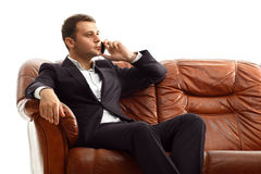 Businessman talking phone sitting on the couch Stock Photos