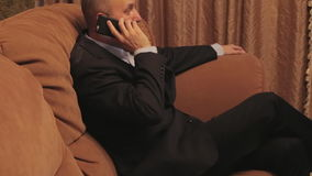 Businessman talking by phone sitting at home on sofa. stock footage