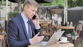 Businessman Talking on Phone while Sitting in Outdoor Cafe stock video