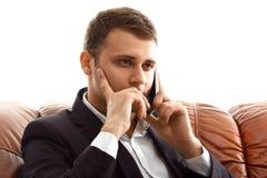 Businessman talking phone sitting on the sofa Stock Photos