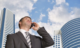 Businessman talking on the phone. Skyscrapers and Royalty Free Stock Image
