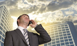 Businessman talking on the phone. Skyscrapers and Stock Photos