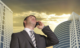 Businessman talking on the phone. Skyscrapers and Stock Image