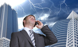 Businessman talking on the phone. Skyscrapers and Royalty Free Stock Images