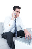 businessman talking on the phone on the sofa with his laptop Royalty Free Stock Photo