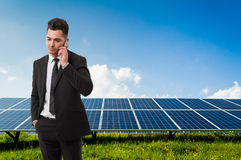 Businessman talking on the phone on solar power panels backgroun Royalty Free Stock Photography