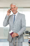 Businessman talking on phone. Businessman standing with luggage using his smartphone in airport. Portrait of a senior business man talking on mobile phone at Royalty Free Stock Photography