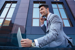 Businessman talking on the phone and using laptop Royalty Free Stock Photo
