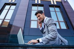 Businessman talking on the phone and using laptop Royalty Free Stock Photos
