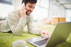 Businessman talking on phone while working on laptop Royalty Free Stock Photography