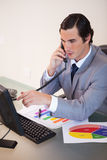 Businessman talking on the phone while working on statistics Royalty Free Stock Photos