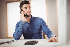 Businessman talking on phone. Young businessman talking on mobile phone at office Stock Image