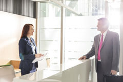 Businessman talking with receptionist in office Stock Images