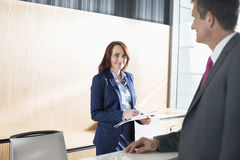 Businessman talking with receptionist in office Royalty Free Stock Images