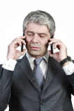Businessman under pressure. Businessman talking simultaneously on two cell phones.under pressure Stock Images
