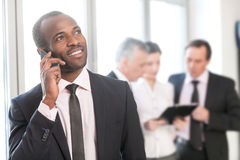 Businessman talking on smart phone with colleagues in the backgr Royalty Free Stock Photography