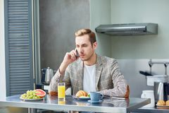 Phoning by breakfast Royalty Free Stock Photos