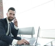 Foreground businessman talking on a smartphone. Businessman talking on a smartphone. Photo with blank space for text Royalty Free Stock Image