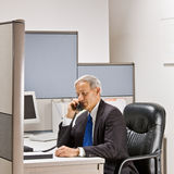 Businessman talking on telephone at desk. Businessman talking on telephone at his desk Royalty Free Stock Image