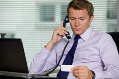 Businessman talking on telephone and looking at card in office Royalty Free Stock Images