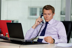 Businessman talking on telephone and looking at card in office Stock Images