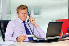 Businessman talking on telephone and looking at card in office Royalty Free Stock Photos