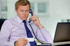 Businessman talking on telephone and looking at card in office Stock Photography